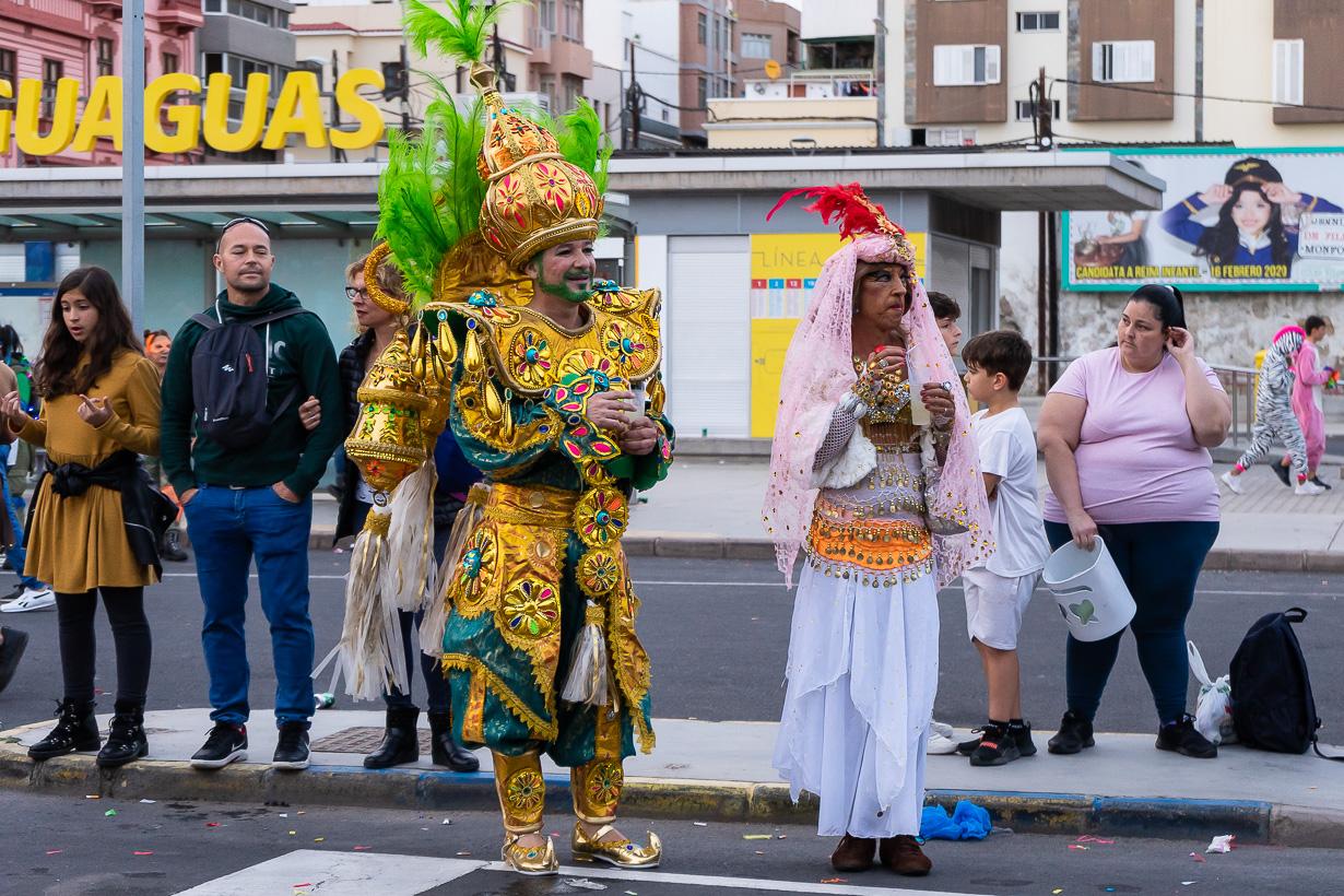 Kultapukuinen karnevaalikulkueen katsoja.